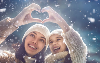 Mother and daughter creating a heart in the snow.